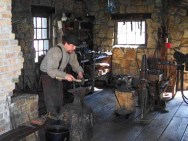 Man blacksmithing inside blacksmith shop