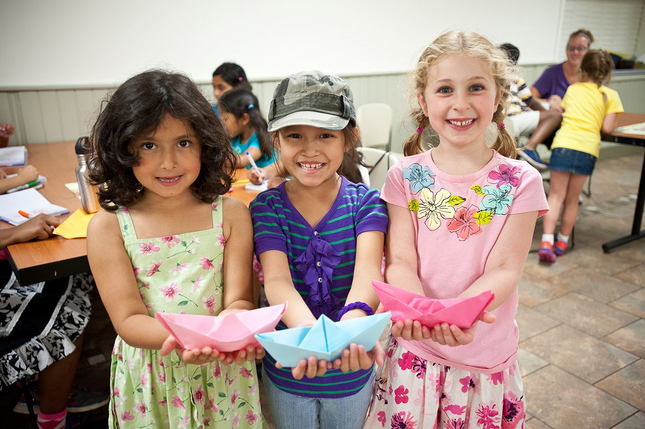 Children showing their origami at Camp Naper