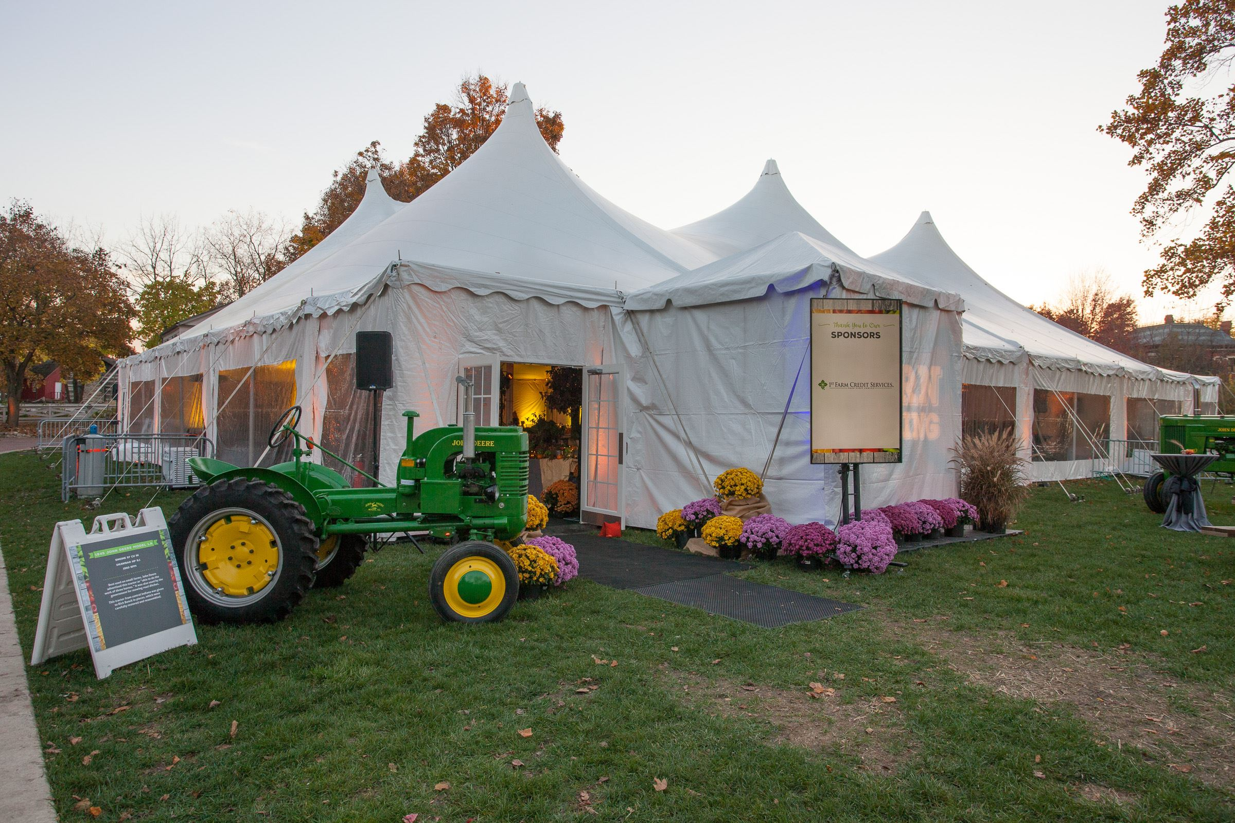 outdoor white tent with tractor at dusk