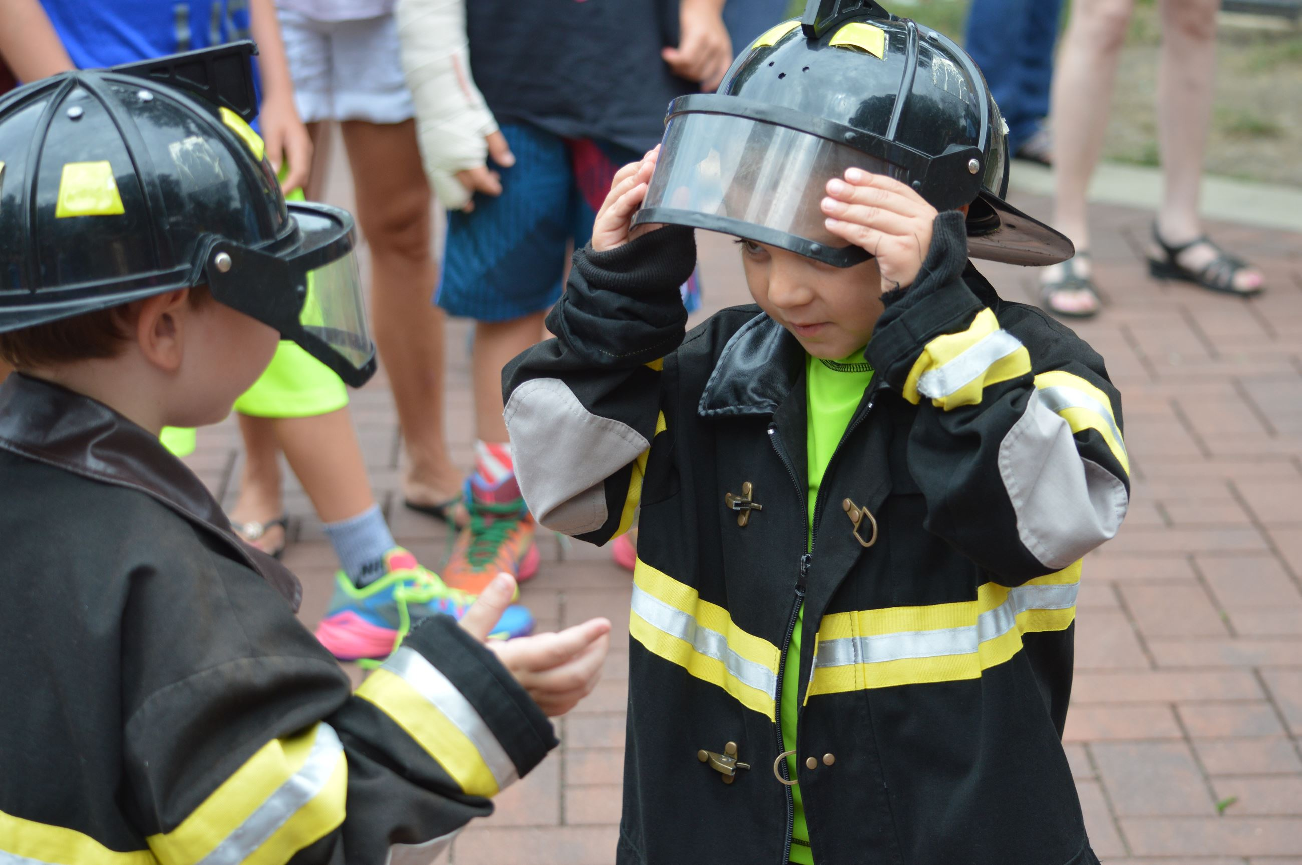 two little boys dressed as firemen putting on helmets