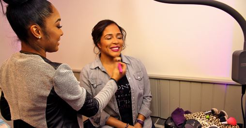 Make-up artist putting blush on a future bride at wedding showcase