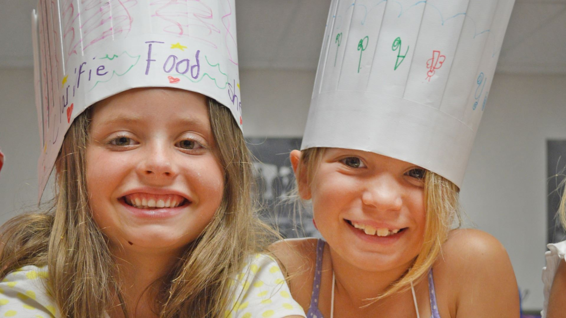 Two young girls wearing paper chef's hats and playing with flour