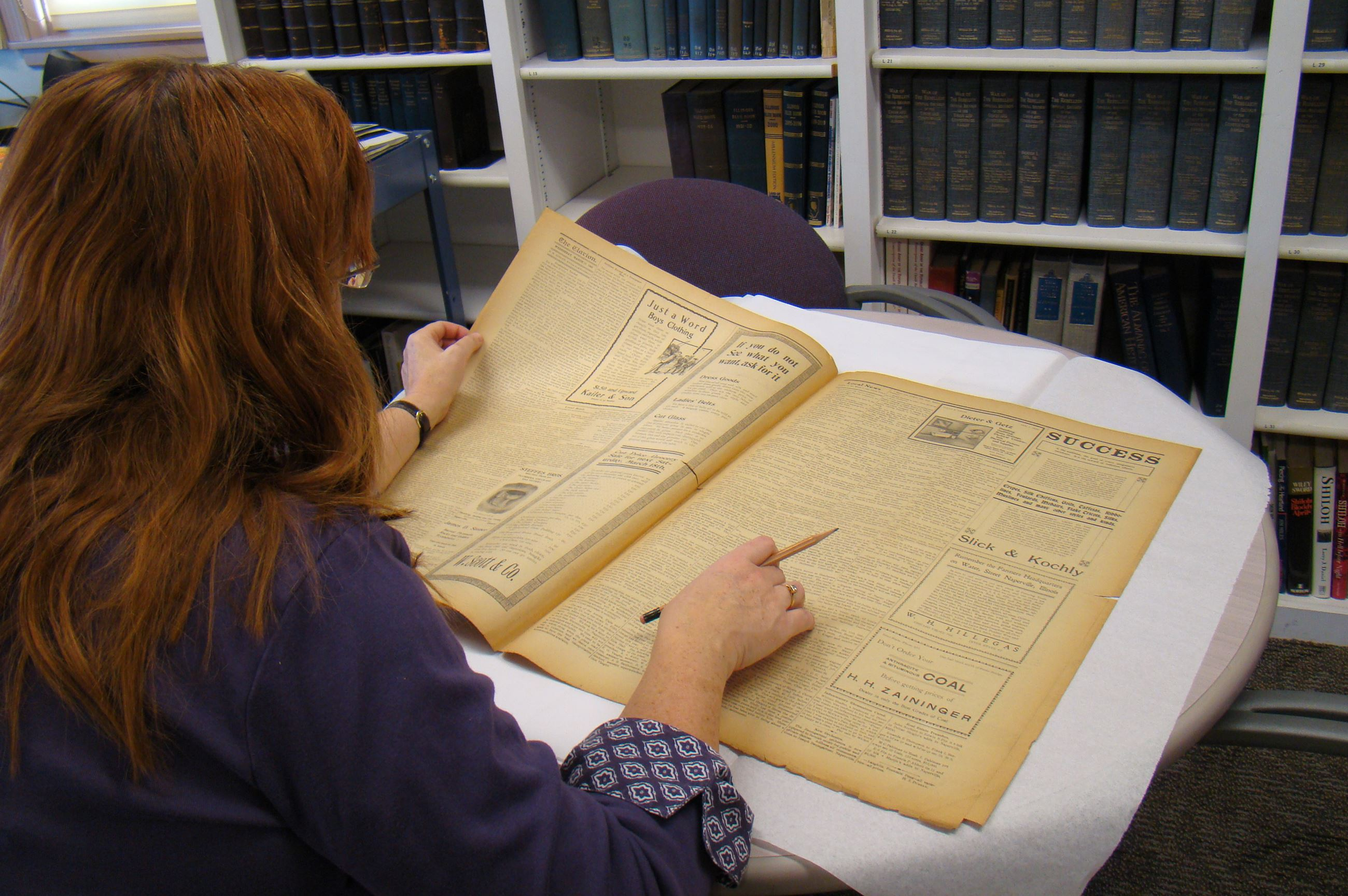 Woman looking at Naperville Clarion in Research Library