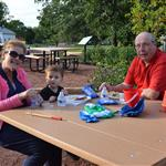 Grandparents with grandson eating a snack at picnic table