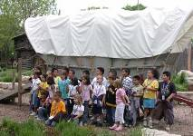 Class in front of a covered wagon